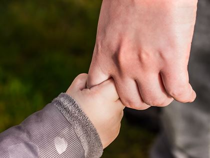 adult holding child's hand